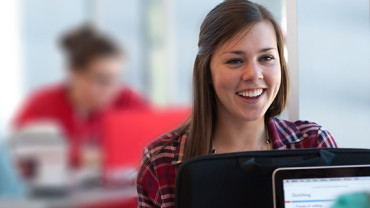 NC State undergraduate sitting at laptop smiling