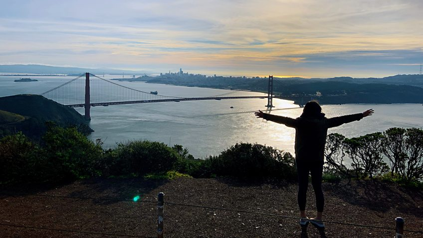 Alice Chen standing on top of a hill overlooking a bridge and water.