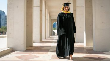Rasha Abdullah wearing black master's regalia outside in a stone pillar hallway.