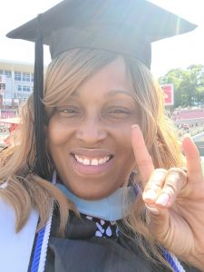 Sherika Lee does the Wolfpack hand sign at the commencement ceremony at Carter-Finley Stadium.