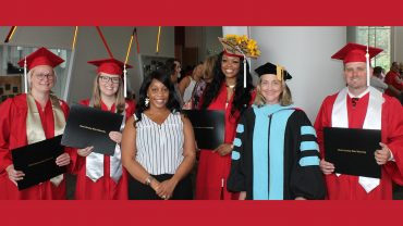 LPS graduates pose for a photo in their regalia with program advisor and faculty member.