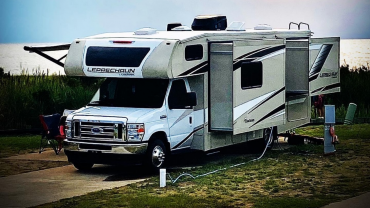 Large Ford RV parked near grass and water.